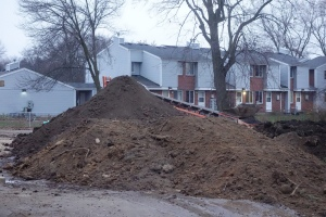 """Occupied residential rental apartment units within a stone's throw, or a silica dust plume from the staging area.  Notice absence of the required soil erosion fencing """"silt socks"""" surrounding the pile of soil."""